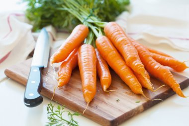raw carrot vegetable on wooden chopping board