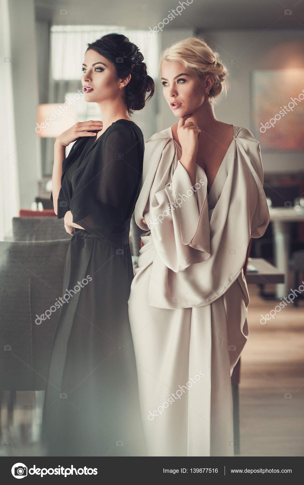 ebdc784462f71f Twee charmante dames in elegante avondjurken in restaurant — Stockfoto