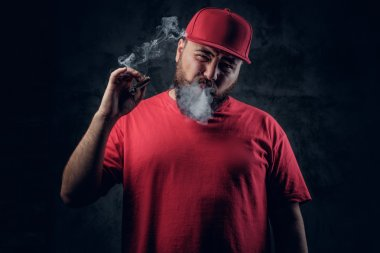 Fatty bearded hipster smoking a cigarette