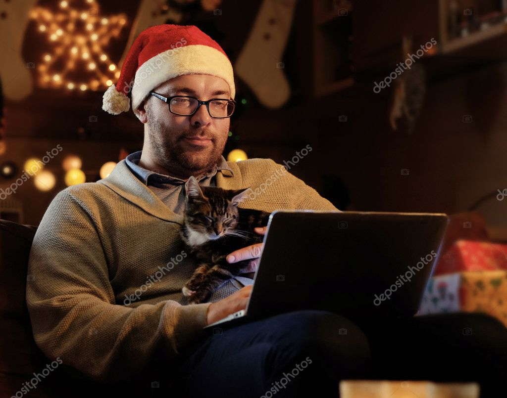 A man holds a cat and working with laptop
