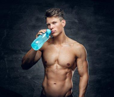 Shirtless muscular male drinking water