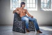 Uomo senza camicia in jeans si siede su una sedia