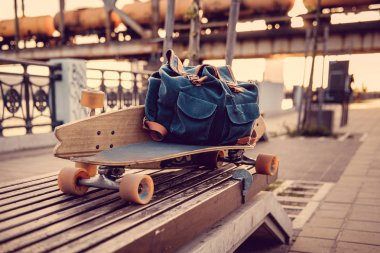 Close up shot of Longboard and backpack on a bench. stock vector