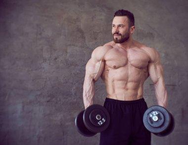 The huge bodybuilder model holds dumbbells
