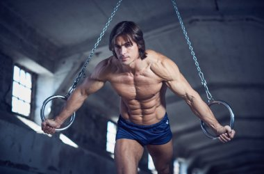 Muscular man posing with gymnastic rings