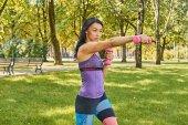 Bruna ragazza sportiva che fa gli allenamenti bicipiti