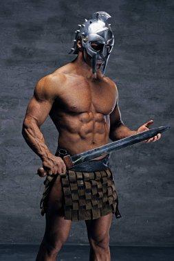 Muscular man in a silver gladiator helmet