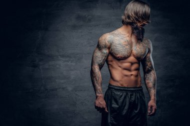 Bearded man with tattooed muscular body