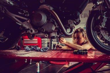 Blonde woman repairing motorcycle