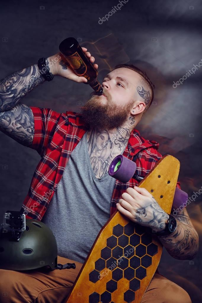 Tattooed skateboarder drinking beer