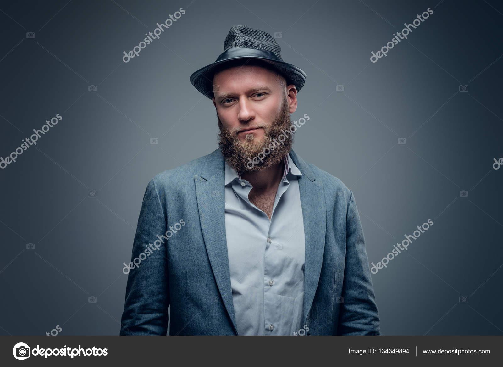 Elegante barbuto uomo in un vestito e cappello su fondo grigio vignette in  feltro — Foto di ... c2a4a5dcab22