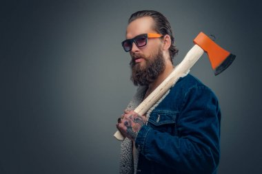 Bearded man holds an axe on his shoulder.