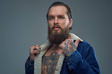 Bearded man with tattooes on arms and chest