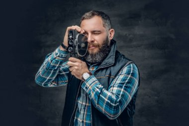 Bearded man holds video camera