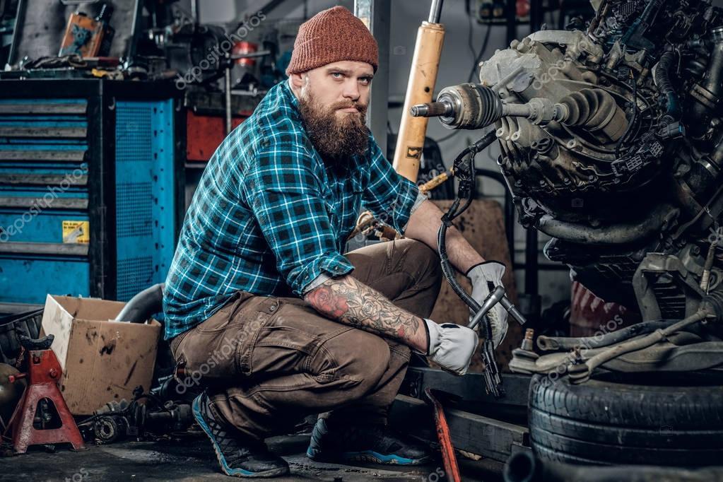 Bearded man repairing the car's engine