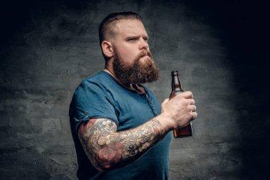 Fat man holds beer bottle