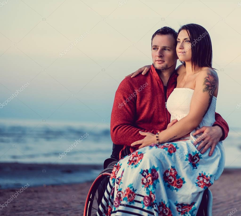 Handicapped couple resting on beach