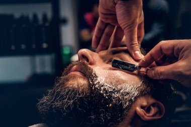 Barber shaving bearded male with a sharp razor