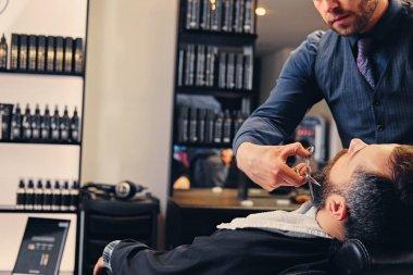 Barber cuts man's beard.