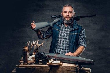 Bearded hunter holds a rifle