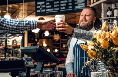 Bearded barista selling coffee to a consumer