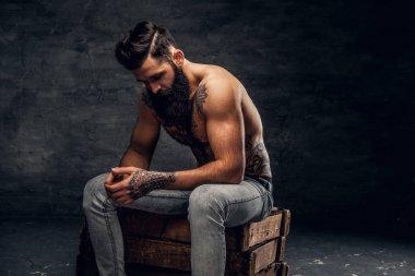 Shirtless bearded man with tattooed torso