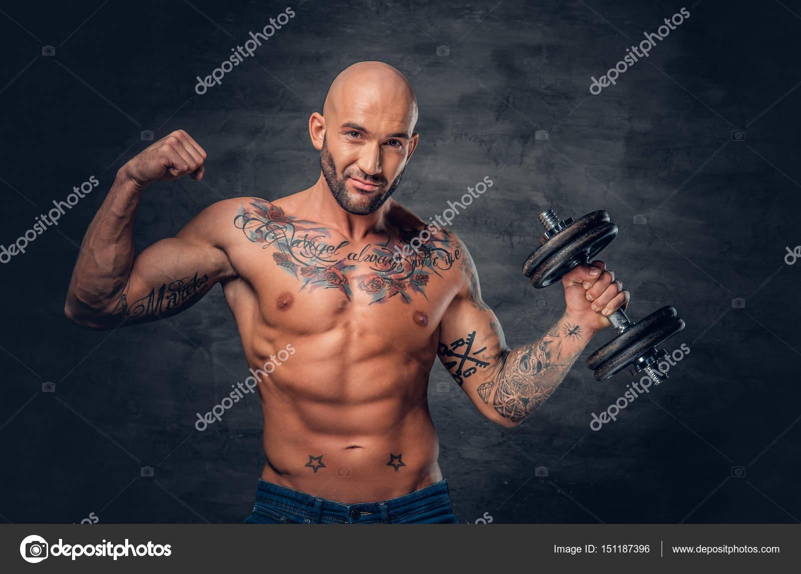sportlicher mann mit tattoos h lt hantel stockfoto. Black Bedroom Furniture Sets. Home Design Ideas