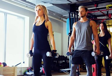 Man and women doing workout with dumbbells