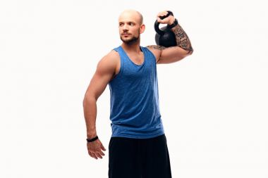 Athletic shaved head male with tattoos on arm holds kettlebell.