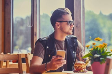 Man using smartphone in a cafe.