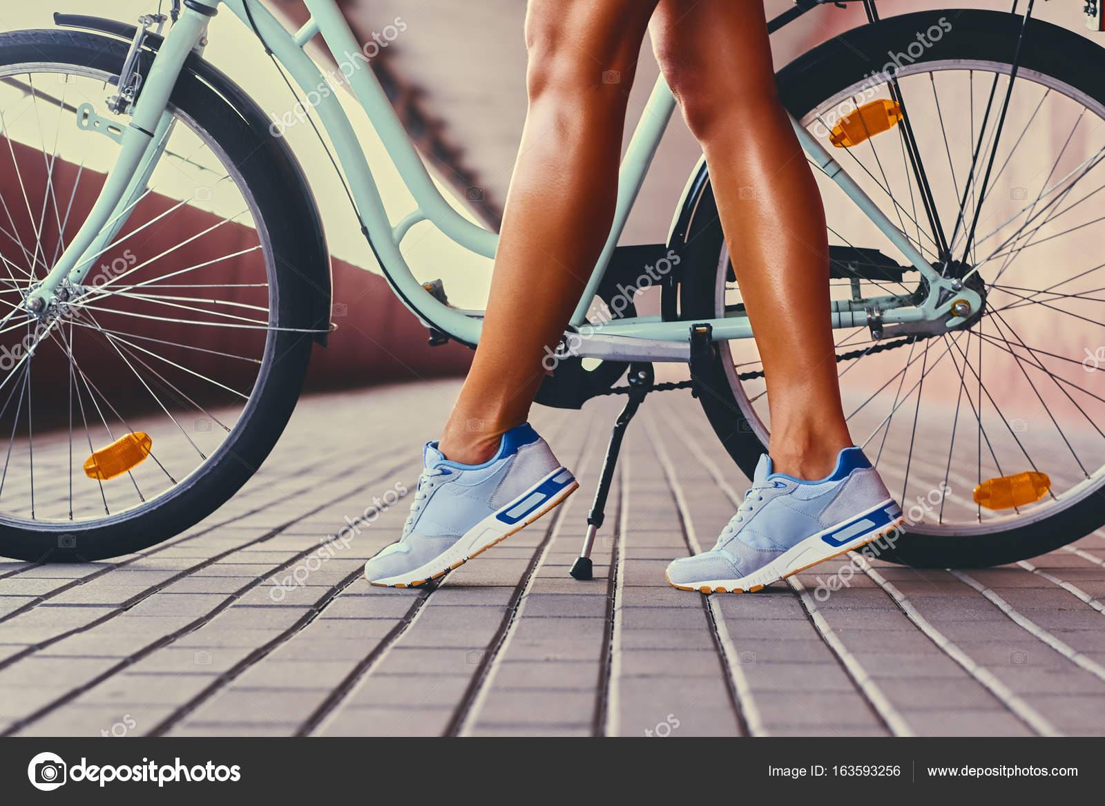 Abbronzare Le Gambe Della Donna E Una Bicicletta Foto Stock