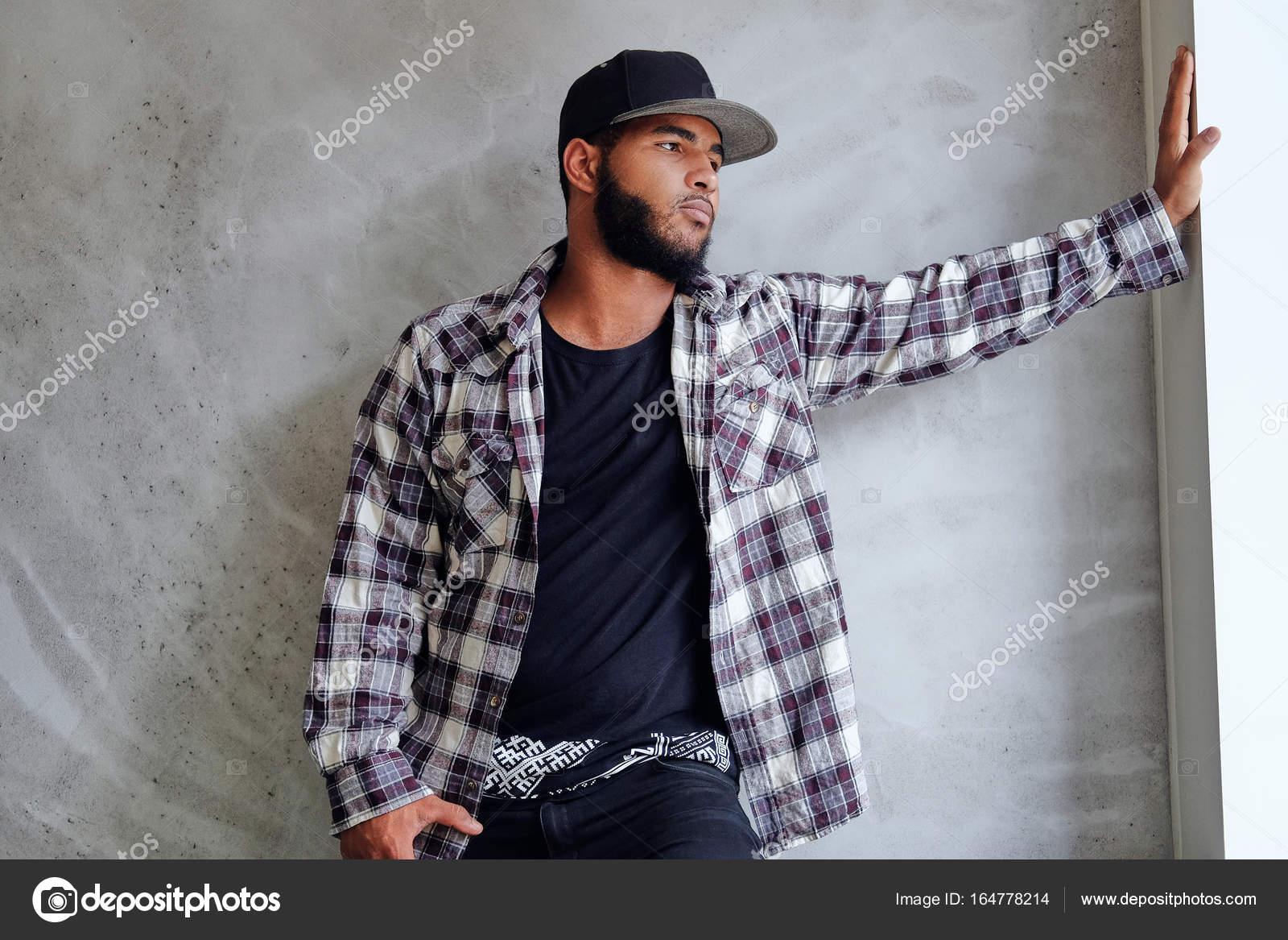 Hipster noir, barbu mâle vêtu d\u0027une chemise de laine et un bonnet, posant  près de fenêtre avec lumière naturelle \u2014 Image de fxquadro