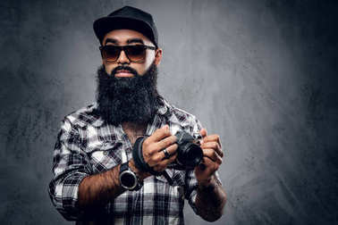 Bearded hipster holds camera