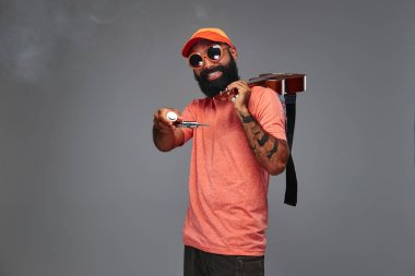 Portrait of a bearded hipster male in an orange cap and sunglasses with electronic pipe and a ukulele on his shoulder, have fun, isolated on grey background.