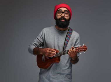 Portrait of a bearded hipster male in a red hat and sunglasses, playing on ukulele. Isolated on grey background.