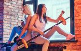Dvě sportovní dívky oblečené v sportswear s činky pózuje v místnosti s interiér podkroví