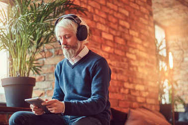 A handsome old man with a gray beard in sweater and jeans using a tablet with headphones sits in a room with loft interior against a brick wall.