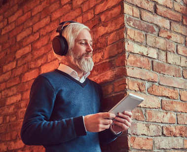 Portrait of an old man with a gray beard in sweater using a tablet and headphones leaning against a brick wall in a room with loft interior.