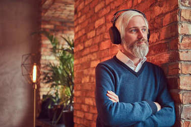 Close-up portrait of a handsome senior man listening to music in headphones leaning against a brick wall in a room with loft interior.