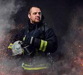 Profesionální hasič oblečený v jednotné, držící ochrannou přilbu v ohni jiskry a kouře na tmavém pozadí