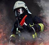 Fotografie Hasič oblečený v uniformě a s kyslíkovou maskou drží červené sekera postavení v ohni jiskry a kouře na tmavém pozadí