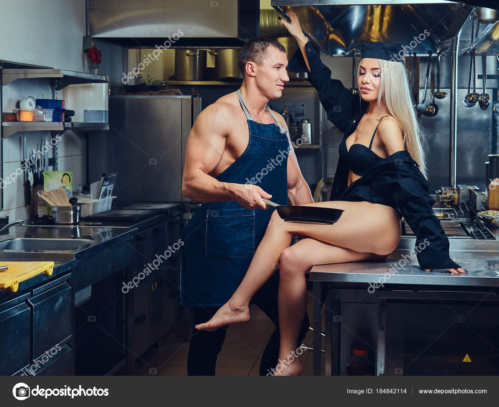 A sexy waitress in lingerie sits on the table, flirts with an attractive  cook.– stock image