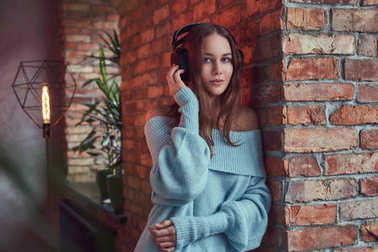 A sensual brunette in a gray sweater with headphones leaning against a brick wall in a room with loft interior.