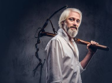 Studio portrait of a smiling handsome old man with a gray beard and white shirt holding a crossbow on shoulder.