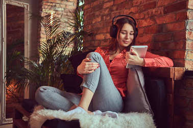 An attractive smiling brunette girl dressed in casual clothes using a tablet while listening to exciting music via good headphones. Relaxing in a room with loft interior.