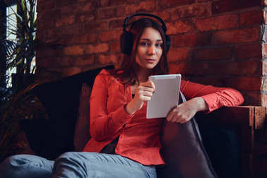 An attractive hipster girl dressed in casual clothes smiling while listening to exciting music via good headphones. Relaxing in a room with loft interior.