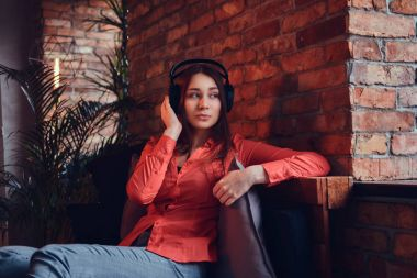 An attractive brunette dressed in casual clothes listen to music via good headphones. Relaxing in a room with loft interior.