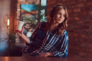 A young charming sensual girl listening to a music in headphones