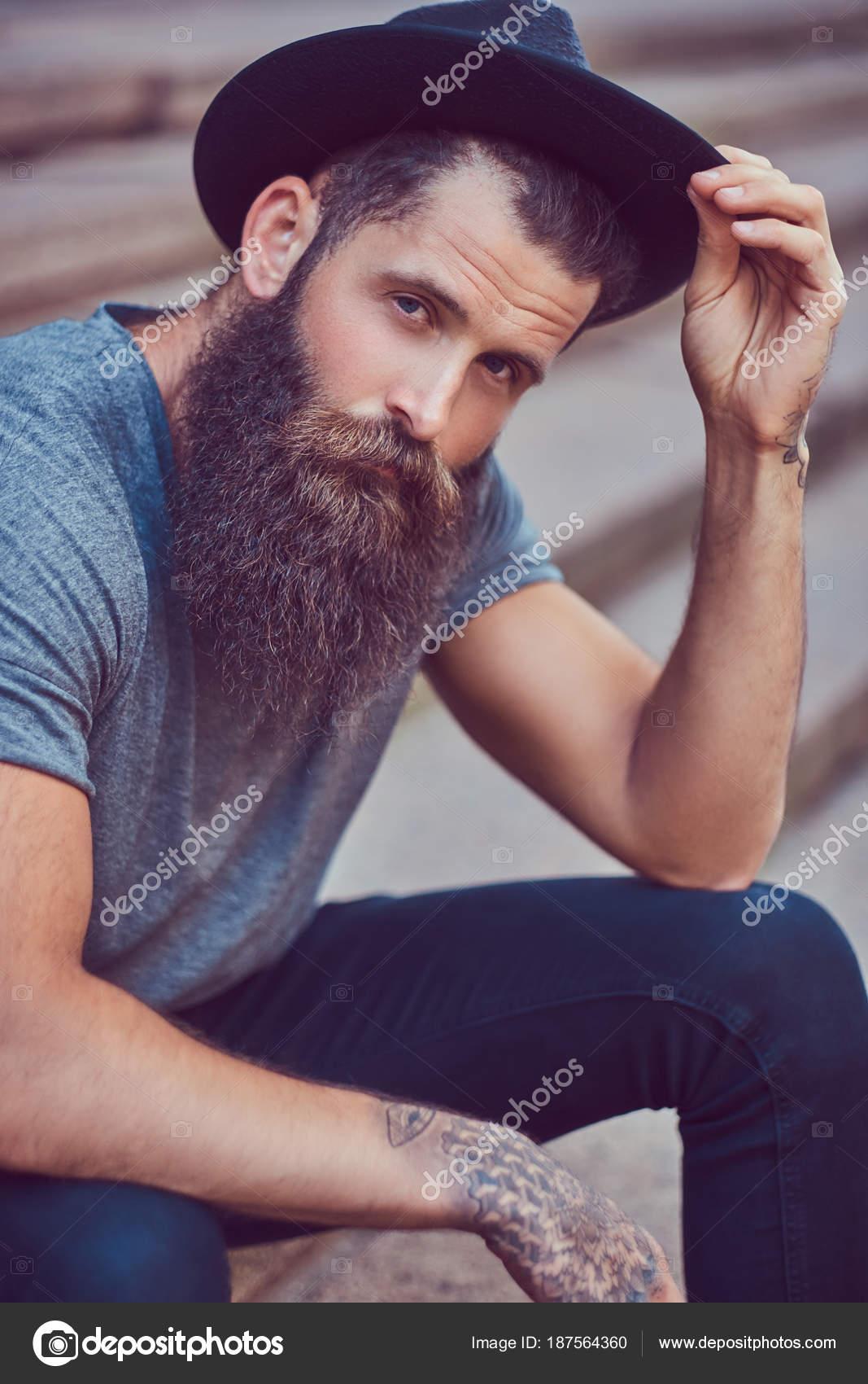 Hombre guapo hipster con una barba con estilo con un tatuaje en los brazos  vestido con ropa casual y sombrero se encuentra en pasos - hombres con  rastas y ... 6538e1a2860