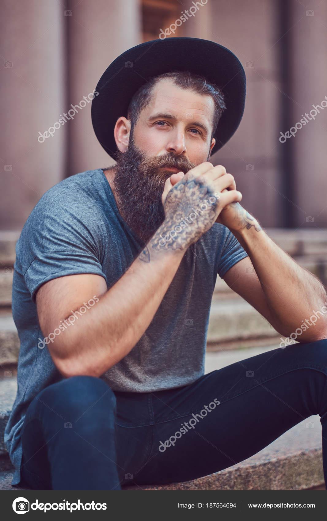 Hombre guapo hipster con una barba con estilo con un tatuaje en los brazos  vestido con ropa casual y sombrero se encuentra en pasos — Foto de fxquadro 7d1b1d6c18f